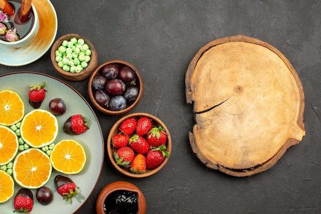 클로즈업 보기 차와 과일 한 컵 차 초콜릿으로 덮인 딸기 다진 오렌지 녹색 사탕과 커팅 보드 옆에 있는 다양한 베리와 과자 그릇