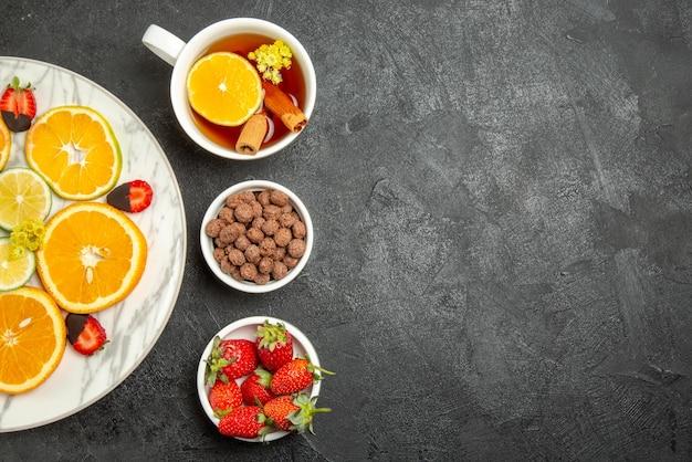 Сверху крупным планом чашка чая и фруктов чашка чая с лимоном и корицей, тарелки орехов и тарелка цитрусовых и клубники в шоколаде на левой стороне темного стола