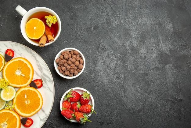 上部の拡大図お茶と果物のカップレモンとシナモンスティックのお茶のカップナッツとイチゴのボウルと柑橘系の果物とチョコレートで覆われたイチゴのプレート