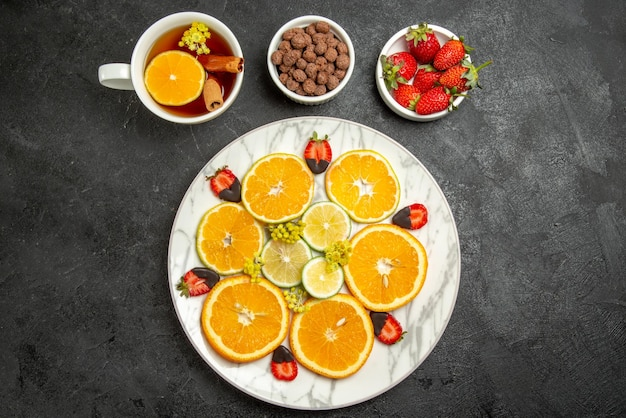탁자 위에 계피와 레몬 접시를 곁들인 차 한 잔 옆에 감귤류 과일과 초콜릿으로 덮인 딸기로 된 차와 과일 접시