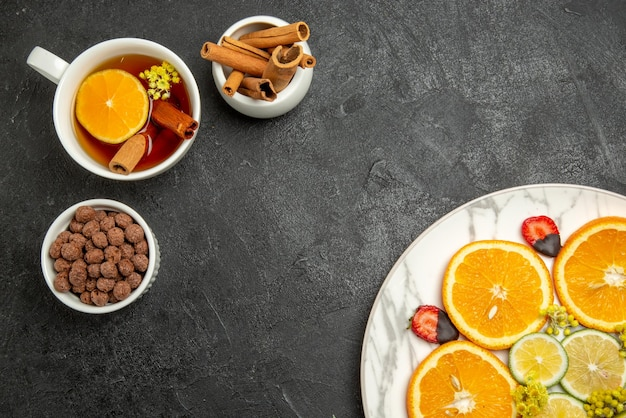 Top close-up view a cup of tea appetizing dish of citrus fruits and strawberries next to the bowls of chocolate and cinnabon sticks and cup of tea with lemon