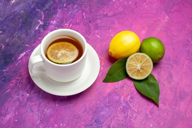 Top close-up view a cup of tea citrus fruits with leaves next to the cup of tasty tea with lemon on the purple-pink table