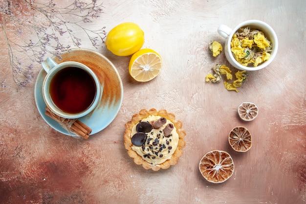 Top close-up view a cup of tea a cup of tea cinnamon lemon cupcake herbs