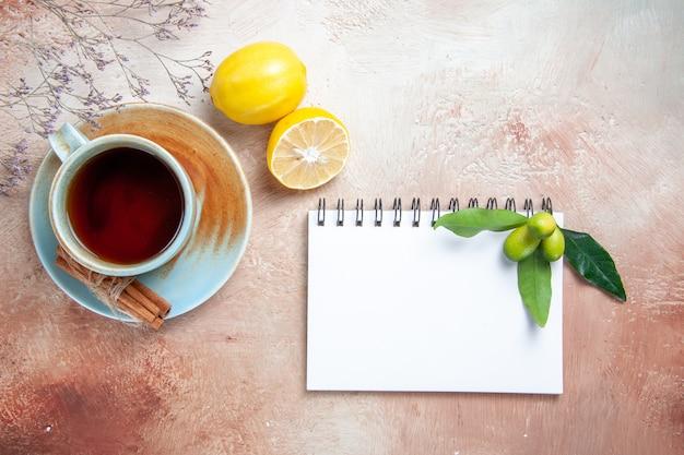 Top vista ravvicinata una tazza di tè una tazza di tè cannella limone bianco notebook