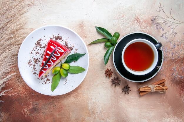 Top vista ravvicinata una tazza di tè una tazza di tè bastoncini di cannella agrumi piatto di torta