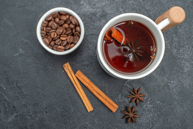 Top close-up view a cup of tea a cup of tea cinnamon sticks star anise coffee beans
