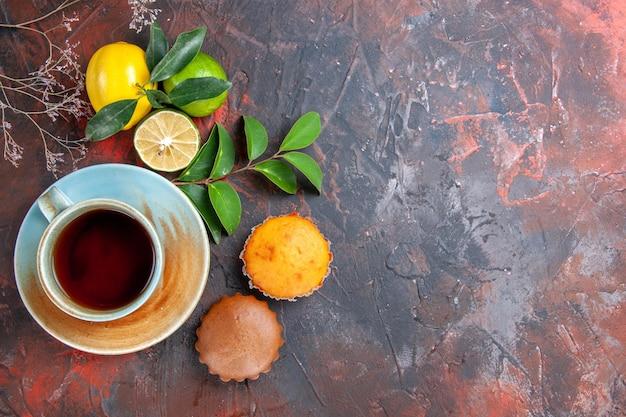 Vista ravvicinata dall'alto una tazza di tè una tazza di tè sul piattino agrumi con foglie cupcakes