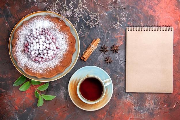 Vista ravvicinata dall'alto una tazza di tè una tazza di tè anice stellato una torta alla cannella quaderno bianco