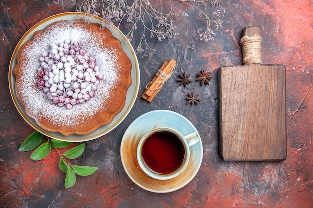 Top close-up view a cup of tea a cup of tea star anise a cake with berries cinnamon the board