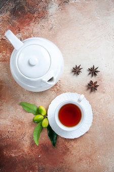 Top close-up view a cup of tea a cup of tea white teapot citrus fruits star anise