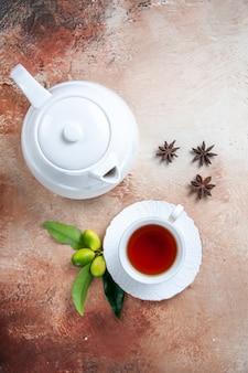 Top vista ravvicinata una tazza di tè una tazza di tè teiera bianca agrumi anice stellato