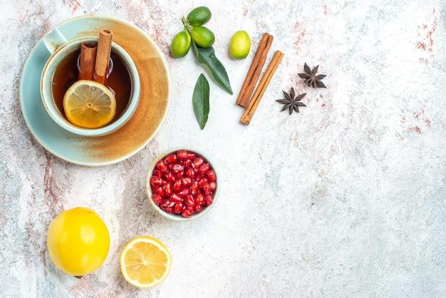 Vista ravvicinata dall'alto una tazza di tè una tazza di tè al limone e cannella sul piattino con agrumi melograno anice stellato e bastoncini di cannella sul tavolo