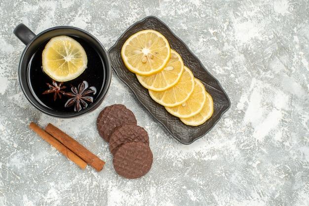 Top vista ravvicinata una tazza di tè una tazza di tè con anice stellato bastoncini di cannella biscotti al limone