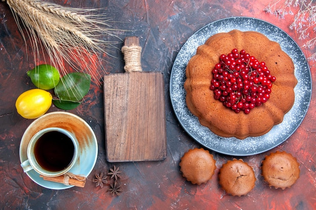 Top close-up view a cup of tea a cup of tea wooden board cupcakes cake with berries lemons