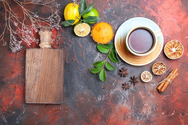 Vista ravvicinata dall'alto una tazza di tè cupcake una tazza di tè nero il tagliere limone anice stellato