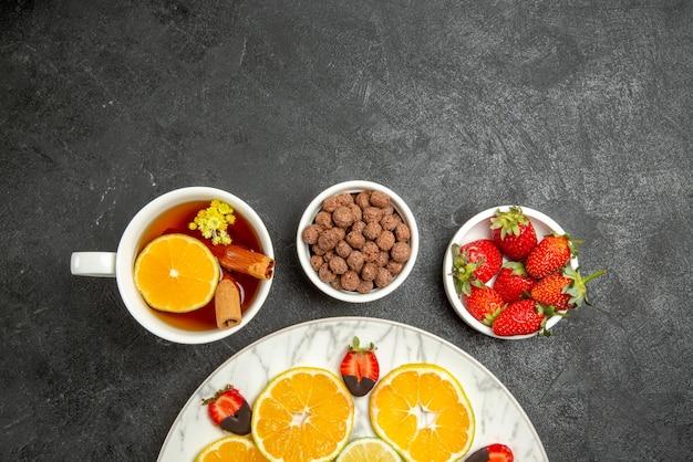 Vista ravvicinata dall'alto tazza di tè e frutta una tazza di tè con cannella e limone piatti di noci e fragole accanto al piatto di agrumi e fragole ricoperte di cioccolato sul tavolo scuro