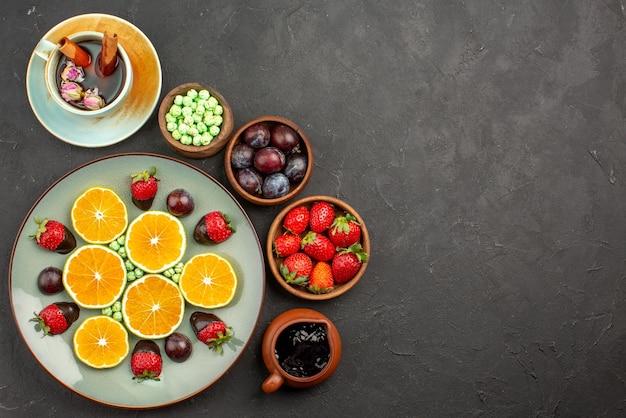 Vista ravvicinata dall'alto tazza di tè e frutta una tazza di tè con cannella piatto di caramelle verdi arancioni tritate fragole ricoperte di cioccolato e ciotole di diversi frutti di bosco e dolci sul tavolo