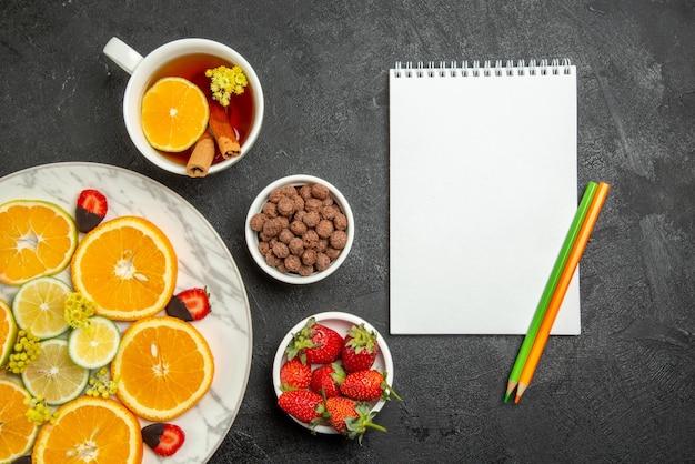 Vista ravvicinata dall'alto tazza di tè e frutta una tazza di tè con limone e cannella ciotole di noci e piatto di agrumi e fragole ricoperte di cioccolato accanto a quaderno bianco e due matite