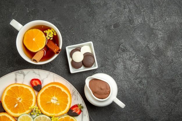 Top close-up view a cup of tea plate of citrus fruits and chocolate-covered strawberries next to the bowls of chocolate and chocolate cream and cup of tea with lemon and cinnabon sticks