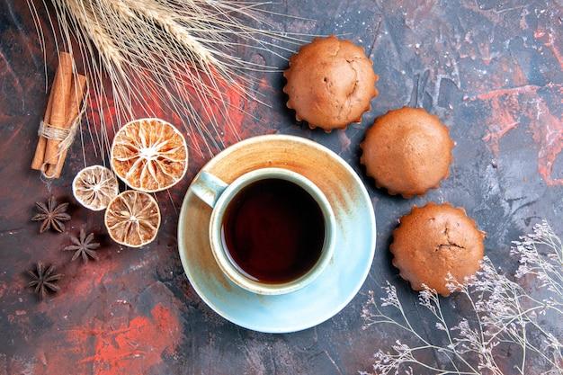 Vista ravvicinata dall'alto una tazza di tè all'anice stellato dolci cupcakes una tazza di tè nero rami di cannella
