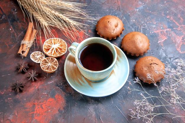 Vista ravvicinata dall'alto una tazza di tè all'anice stellato dolci cupcakes una tazza di tè alla cannella spighe di grano