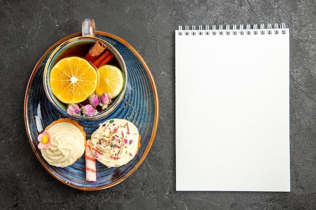 Vista ravvicinata dall'alto una tazza di tè al limone gli appetitosi cupcakes con crema accanto alla tazza di tisana con limone e cannella e taccuino bianco sul tavolo scuro