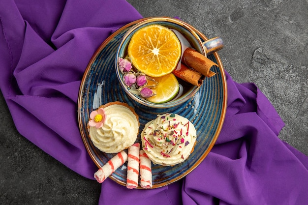 Top close-up view a cup of tea with lemon appetizing cupcakes with a cup of tea on the purple tablecloth on the table