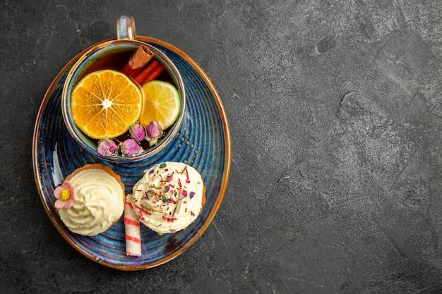 Vista ravvicinata dall'alto una tazza di tè al limone un piattino blu degli appetitosi cupcakes con crema e una tazza di tisana con limone e cannella sul tavolo scuro
