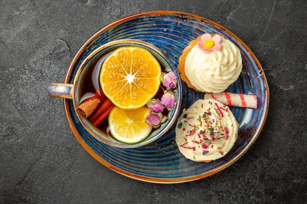 Top close-up view a cup of tea with lemon two appetizing cupcakes with white cream sweets and a cup of with herbs and lemon on the blue saucer on the black table