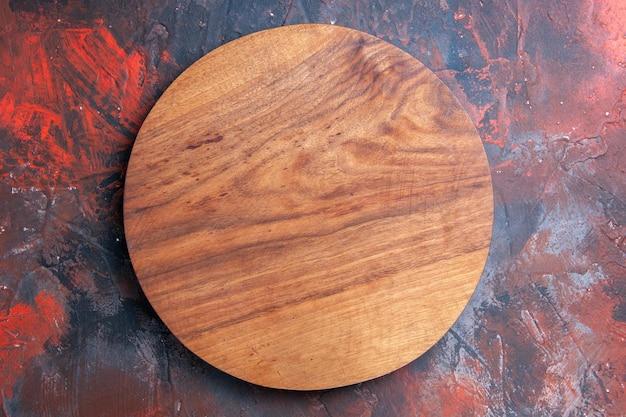 Tagliere in legno con vista ravvicinata dall'alto sullo sfondo rosso-blu