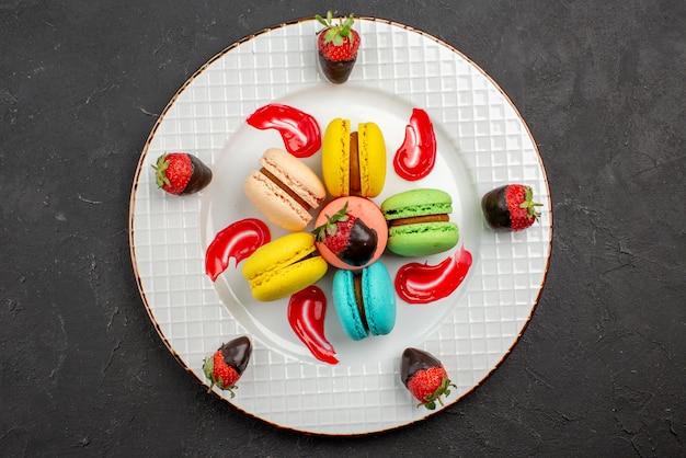 暗いテーブルの上にチョコレートで覆われたイチゴとフランスのマカロンを食欲をそそる上部のクローズアップビューデザート