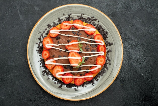 暗いテーブルの中央にある白いプレートにイチゴとチョコレートを添えた上部のクローズアップビューデザートパイ