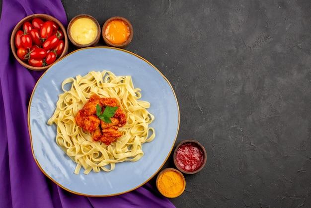 Вид сверху крупным планом блюдо и соусы, аппетитные макаронные изделия, мясо и подливка, а также тарелки с помидорами и соусами на фиолетовой скатерти на темном столе