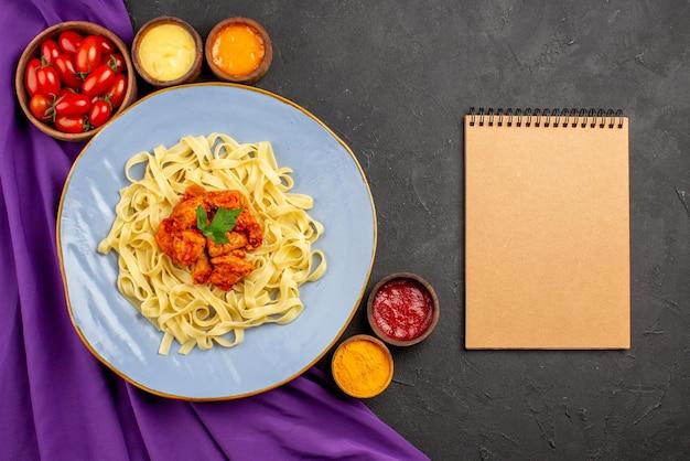 Вид сверху крупным планом блюдо и соусы, аппетитные макароны, мясо и подливка рядом с блокнотом с кремом и тарелками помидоров и соусов на фиолетовой скатерти на темном столе