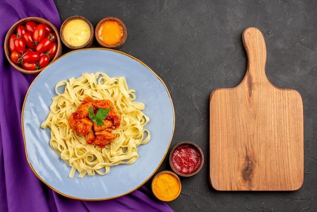 Вид сверху крупным планом блюдо и соусы, аппетитные макароны, мясо и подливка рядом с деревянной разделочной доской и тарелками с помидорами и соусами на фиолетовой скатерти на темном столе