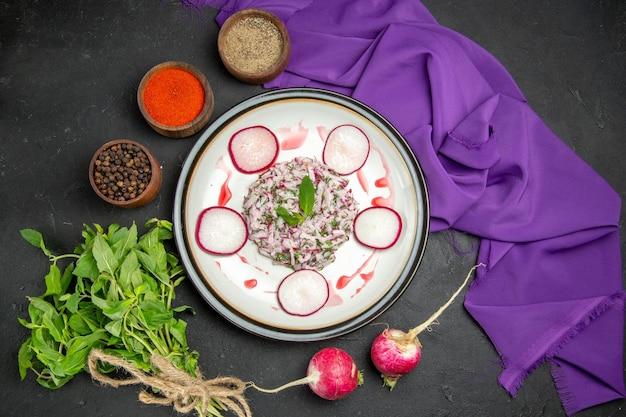 Vista ravvicinata dall'alto un piatto un piatto appetitoso di spezie colorate raddish sulla tovaglia viola