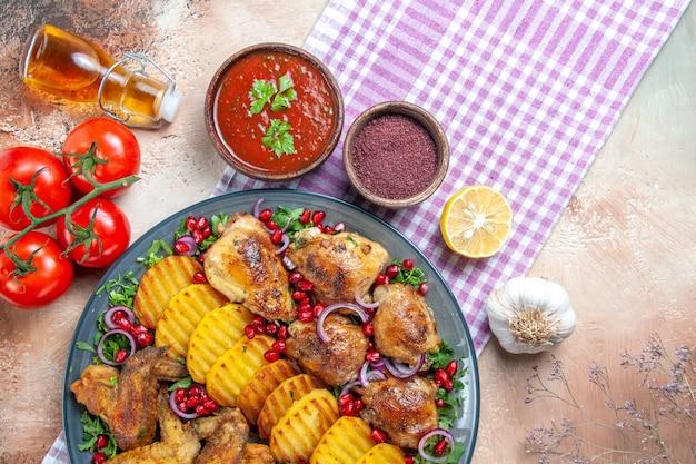 Top vista ravvicinata piatto ali di pollo patate olio pomodori con pedicelli spezie sulla tovaglia