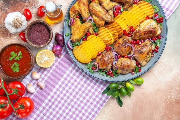 Top vista ravvicinata piatto pollo con patate salsa limone pomodori spezie olio aglio