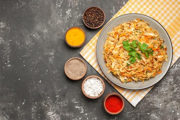 Top piatto vista ravvicinata piatto di cavolo sulla tovaglia ciotole di spezie colorate