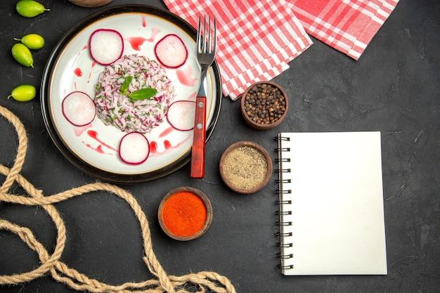 Vista ravvicinata dall'alto un piatto di forchetta rossastra ciotole di spezie il quaderno della tovaglia a scacchi