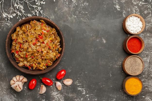 Vista ravvicinata dall'alto piatto di fagiolini piatto di fagiolini ciotole di spezie aglio sul tavolo nero