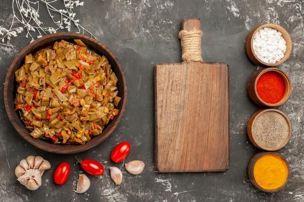 Vista ravvicinata dall'alto piatto di fagiolini piatto di fagiolini e pomodori nel piatto quattro ciotole di spezie tagliere e aglio sul tavolo nero