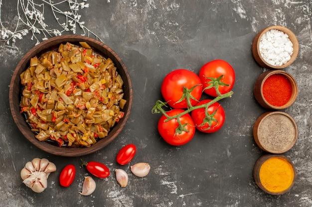 Vista ravvicinata dall'alto piatto di fagiolini piatto di fagiolini e pomodori nel piatto quattro ciotole di spezie aglio e pomodori con pedicelli sul tavolo nero