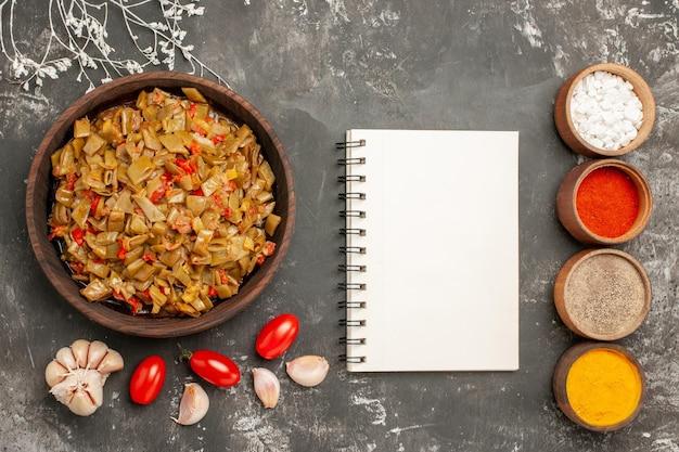 Vista ravvicinata dall'alto piatto di fagiolini piatto di fagiolini e pomodori nel piatto quaderno bianco ciotole di spezie aglio sul tavolo nero