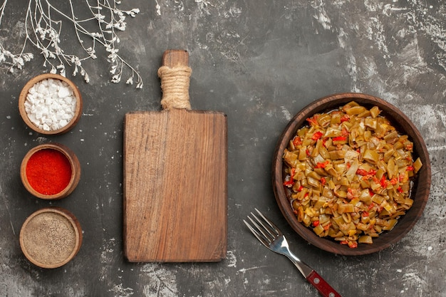 Vista ravvicinata dall'alto piatto di fagiolini tre ciotole di spezie accanto al tagliere fagiolini e pomodori nel piatto e forchetta sul tavolo nero