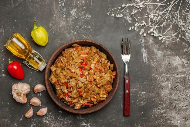식탁에 있는 녹색 콩과 토마토 접시와 포크 옆에 있는 콩 피망 기름 마늘 한 병