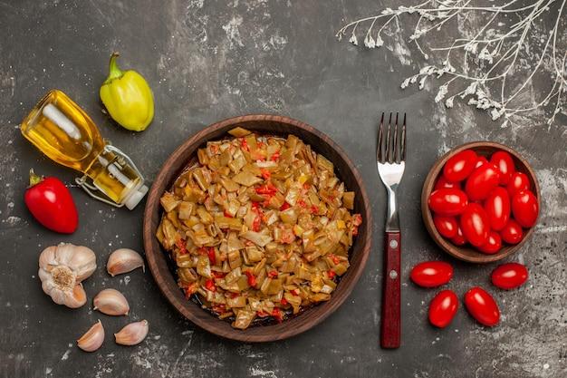 豆のトップクローズアップディッシュトマトフォークのボウルとテーブルの上のサヤインゲンとトマトのプレートの横にあるボトルガリックの2種類のピーマンオイル