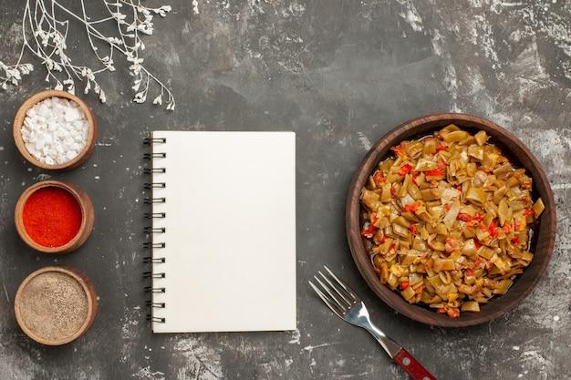 プレートの白いノートのサヤインゲンとトマトの横にあるスパイスのボウルと黒いテーブルのフォークの上部の拡大図の皿