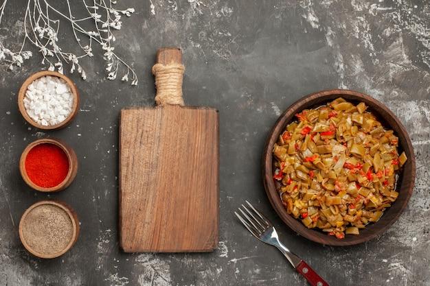 さやいんげんのトップクローズアップディッシュまな板の横にある3杯のスパイス皿にさやいんげんとトマト、黒いテーブルにフォーク