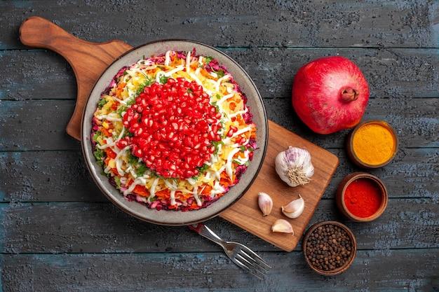 Вид сверху крупным планом блюдо на борту блюдо из аппетитного граната в тарелке и чеснока на разделочной доске рядом с различными специями, вилкой и гранатом